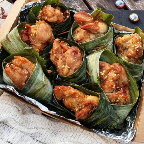 A box of chicken pieces wrapped in pandan leaves. Pandan Chicken from Jai Siam, delivered islandwide in Singapore powered by Oddle.