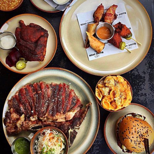 A flatlay of various dishes, such as steak, a burger, coleslaw and more. Premium Meal for 2 from Meatsmith, delivered islandwide in Singapore powered by Oddle. For party food delivery Singapore.